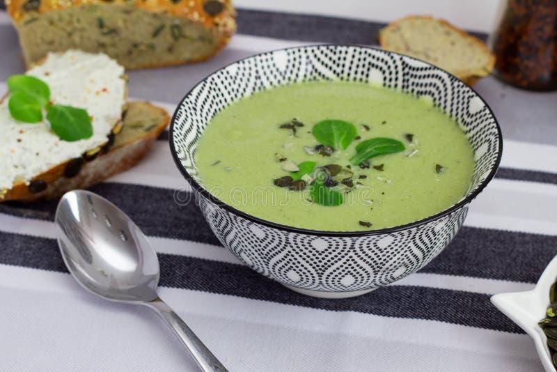 Bunken av broccoli skummar soppa, kornbröd med pumpafrö och skeden på tabellen, sunt vegetariskt ätabegrepp Allsidiga di royaltyfri fotografi
