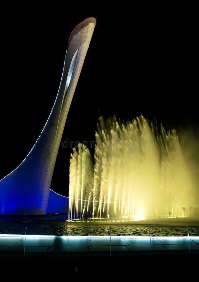 Bunken av den olympiska flamman Firebird och den sjungande springbrunnen i det olympiskt parkerar i aftonen arkivfoton