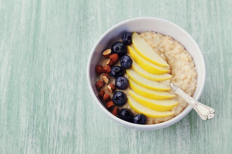 Bunken av havremjölhavregröt med äpplet, bär, honung och mandeln på den lantliga tabellen, bantar frukosten arkivfoto