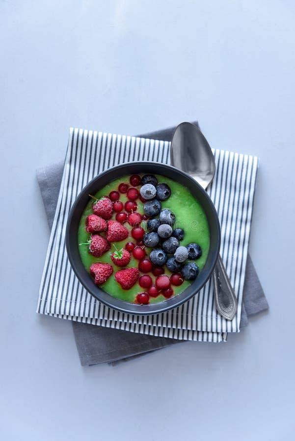 Bunken för frukostkiwismoothien överträffade med det djupfrysta hallonet, blåbäret och den röda vinbäret på grå träbakgrund Top b royaltyfria bilder