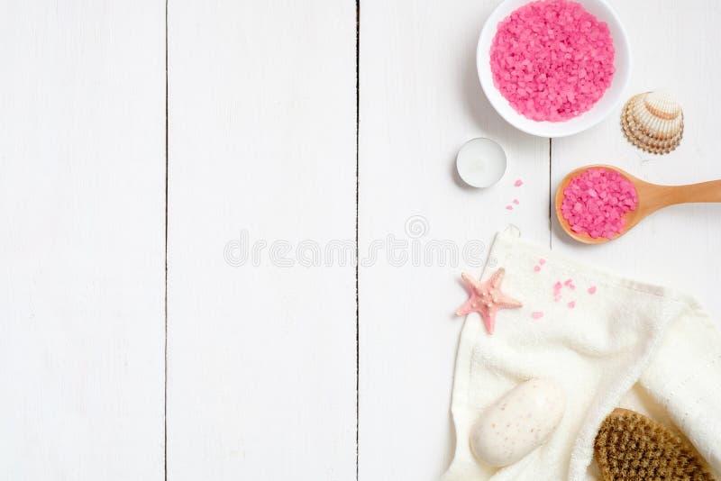 Bunken med det rosa badet saltar, träskeden, handduken, tvålsjöstjärnan, brunnsortborste på träyttersida Det Spa tillvägagångssät royaltyfri bild