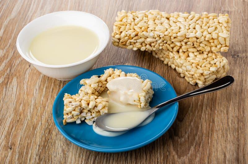 Bunken med kondenserat mjölkar, mjölkar hällt på brutna pustaa ris, sked i tefatet, pustt ris på tabellen royaltyfria bilder