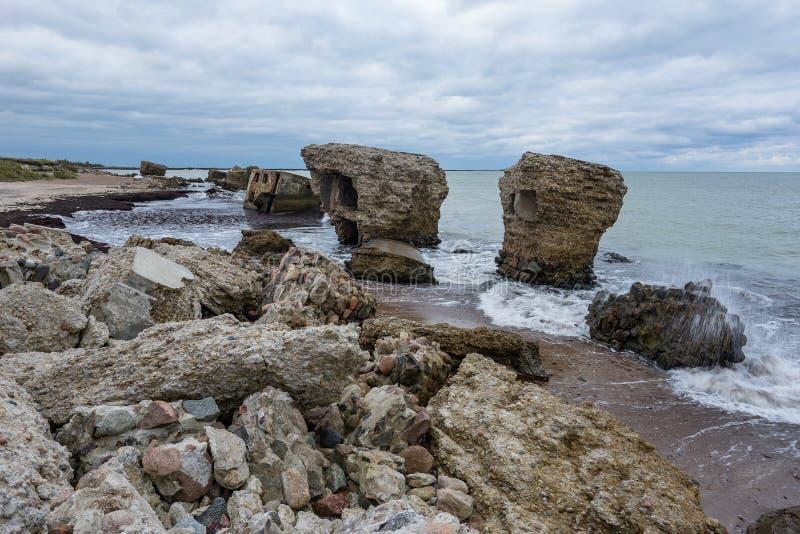 Bunker de praia Liepaja Casa de tijolos, água macia, ondas e pedras Instalações militares abandonadas em ruínas num mar tempestuo imagem de stock royalty free