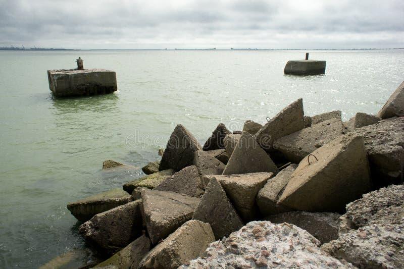 Bunker de praia Liepaja Casa de tijolos, água macia, ondas e pedras Instalações militares abandonadas em ruínas num mar tempestuo imagens de stock