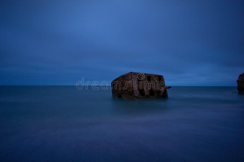 Bunker de praia Liepaja Casa de tijolos, água macia, ondas e pedras Instalações militares abandonadas em ruínas num mar tempestuo fotografia de stock