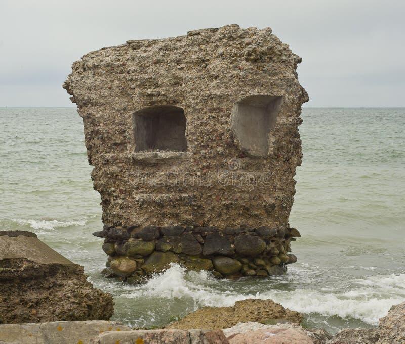 Bunker de praia Liepaja Casa de tijolos, água macia, ondas e pedras Instalações militares abandonadas em ruínas num mar tempestuo fotos de stock royalty free