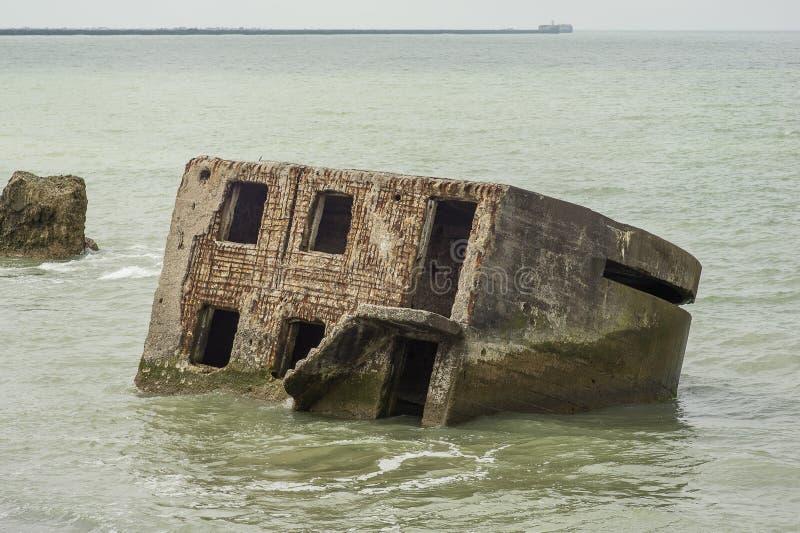 Bunker de praia Liepaja Casa de tijolos, água macia, ondas e pedras Instalações militares abandonadas em ruínas num mar tempestuo foto de stock