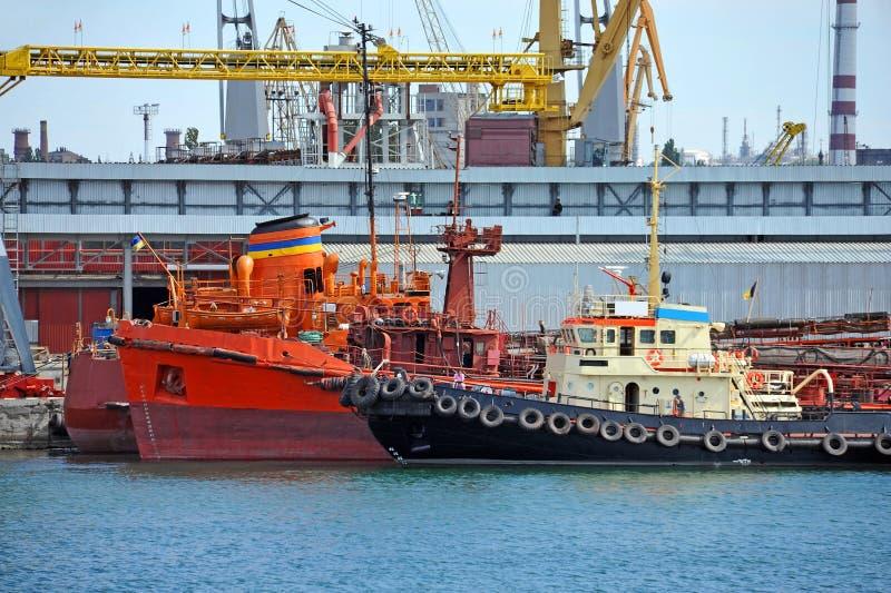 Bunkieru tugboat pod portowym żurawiem i statek obrazy stock