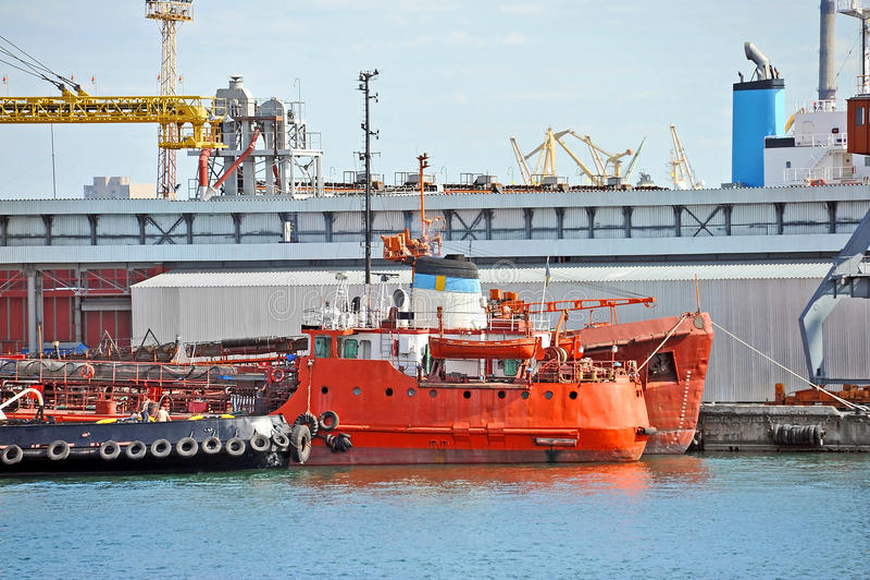 Bunkieru tugboat pod portowym żurawiem i statek obrazy royalty free