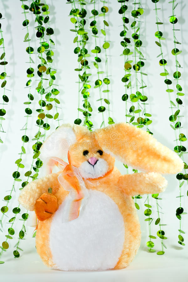 Bunny. An orange stuffed toy bunny holding a stuffed carrot with floppy ears and sparkly decorations behind it on a white background stock photo
