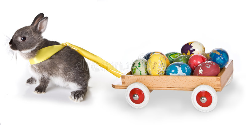 Bunny with cart. Little gray easter bunny pulling a cart filled with easter eggs stock photo