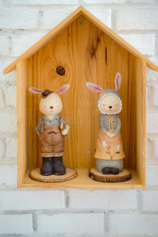 Bunny house on white background. White rabbit in wood house royalty free stock photo
