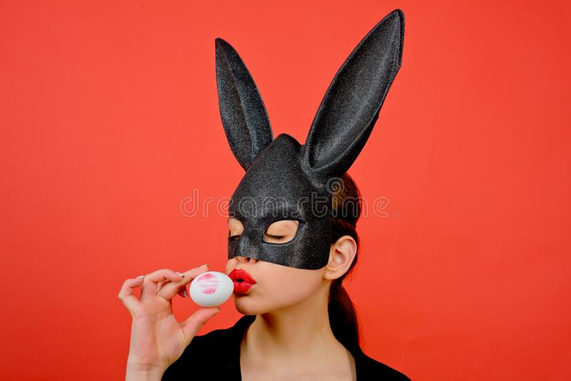 Bunny mask woman. Female mouth kiss. Lipstick kiss print. Red lip imprint on easter egg on red background. Young girl stock photo