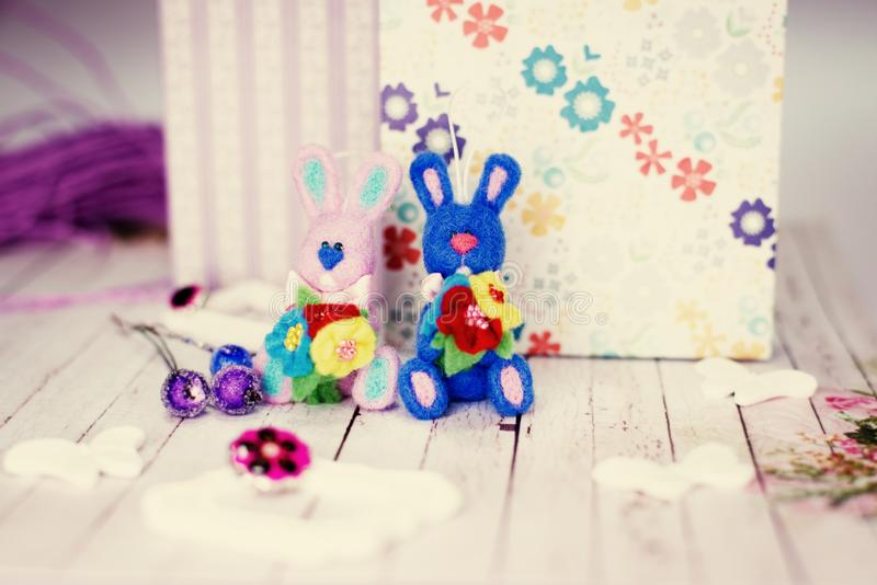 Bunny rabbits, gift boxes and artistic decorations on wooden table background. Knitted bunny rabbits, gift boxes and artistic decorations on wooden table royalty free stock images