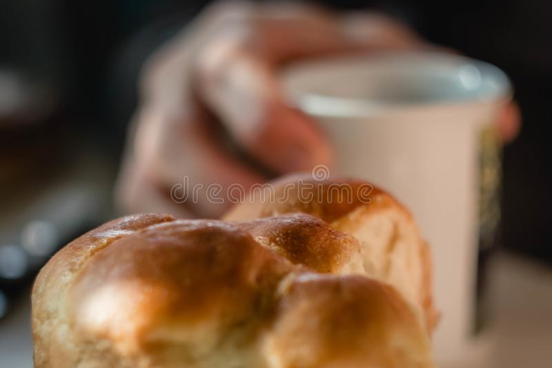 Buns and cup of fruit tea on white wooden table. man hands making tea, stirring slowly with spoon. delicious nourishing breakfast. Chocolate croissants, bun and royalty free stock photos