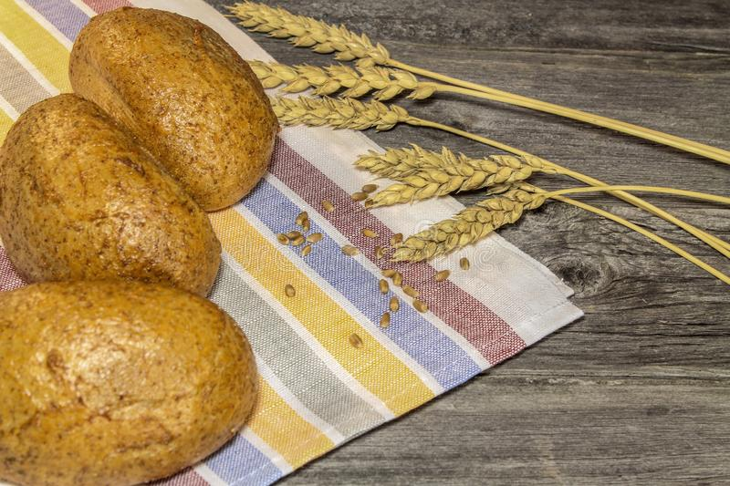 Buns, grains and ears of wheat on a wooden table royalty free stock photos