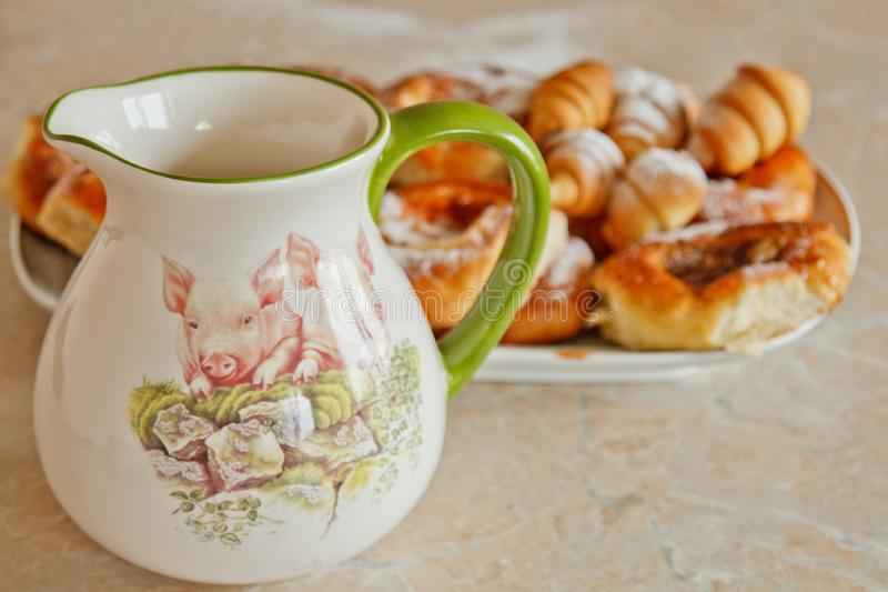 Buns in a plate full of freshly baked bagels dusted with icing sugar with a ceramic jug on the kitchen table. cooking baking. stock photos