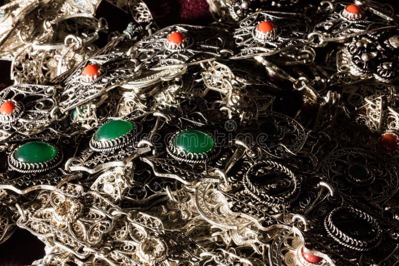 Bunt серебряных ювелирных изделий с зелеными и красными драгоценными камнями стоковые фотографии rf
