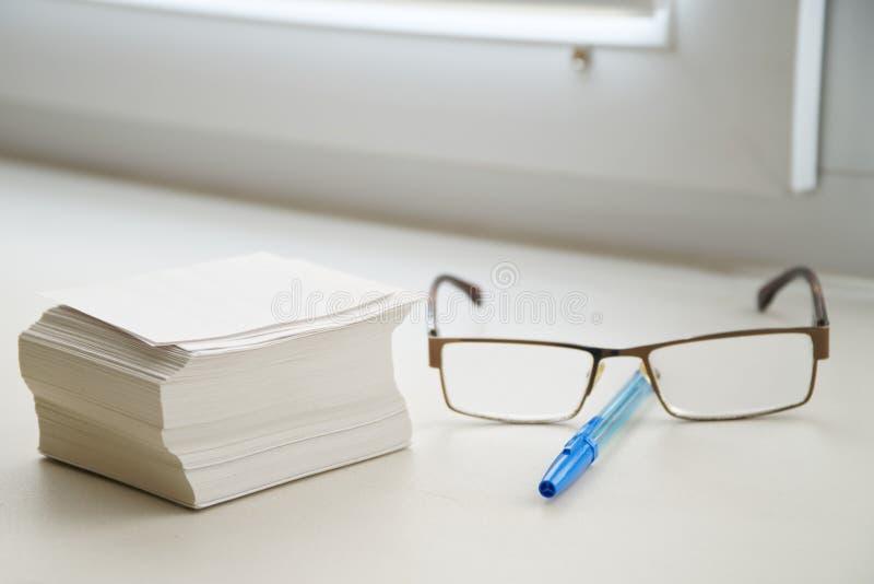 Bunt av ark för anmärkningar, exponeringsglas och en pennlögn på fönsterbrädan i kontoret Arbete på att katalogisera fotografering för bildbyråer
