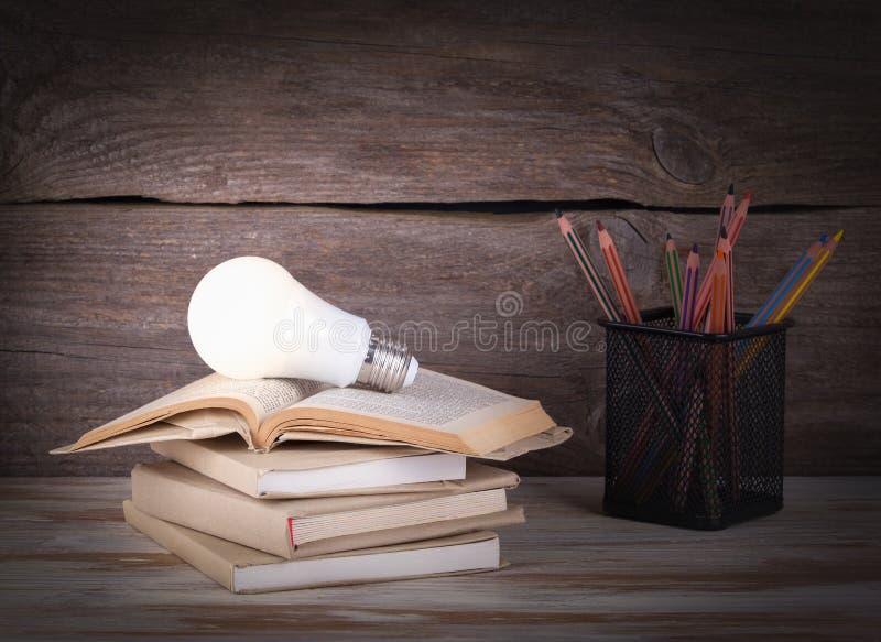 Bunt av böcker, ljus kula och blyertspennor på trätabellen royaltyfri bild