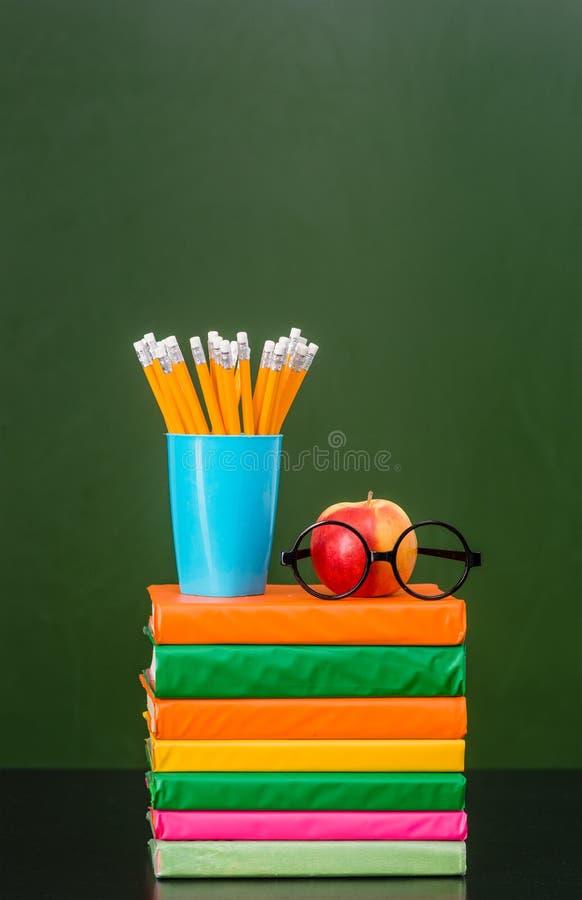 Bunt av böcker med äpplet och blyertspennor nära den tomma gröna svart tavlan royaltyfri bild