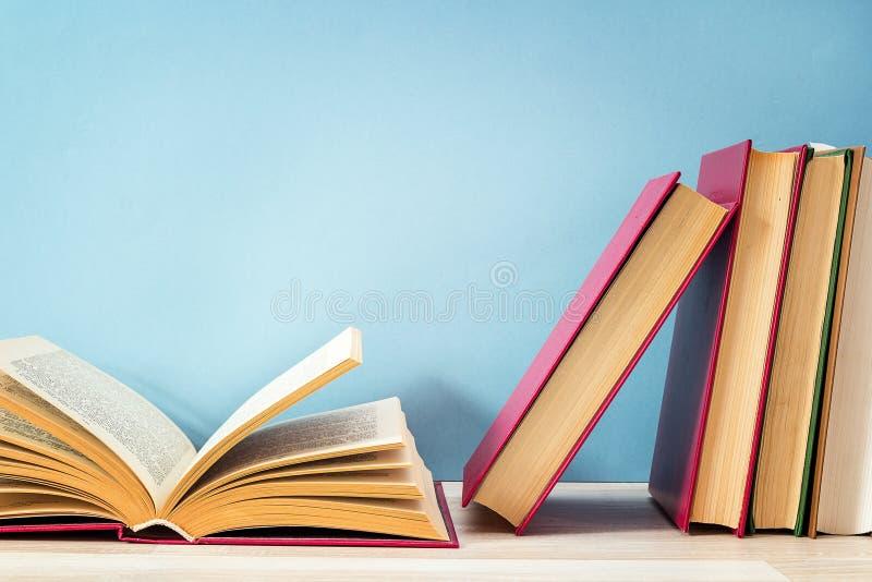 Bunt av böcker med den öppna boken på mot en blå bakgrund kopia arkivbild