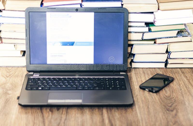 Bunt av böcker, smartphone, bärbar dator, affärsbakgrund för exponeringsglas i regeringsställning för utbildning som lär begrepp arkivbilder