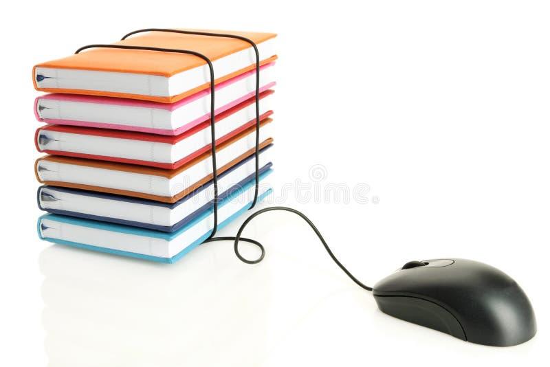 Bunt av böcker som förbinder till en datormus arkivfoton