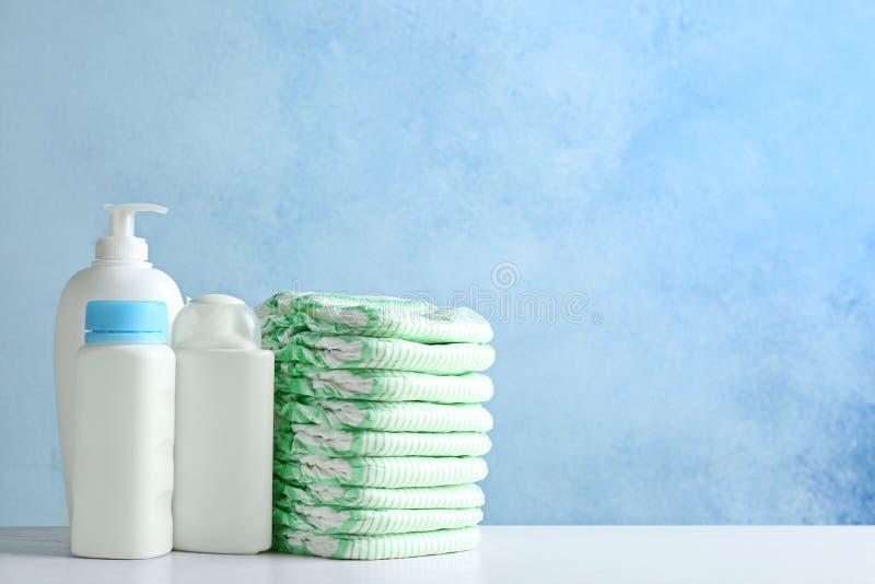 Bunt av blöjor och toalettartiklar på tabellen mot färgbakgrund Behandla som ett barn tillbeh?r royaltyfri bild