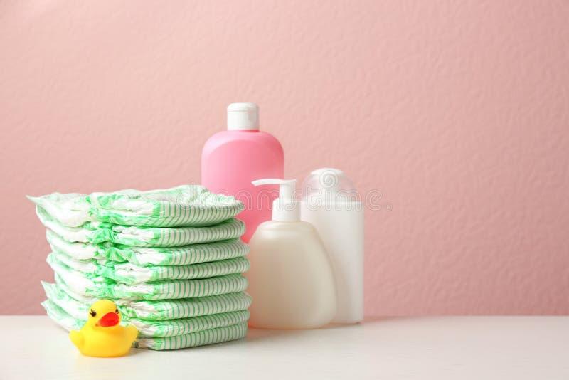 Bunt av blöjor, toalettartiklar och leksakanden på tabellen mot färgbakgrund, utrymme för text arkivfoton