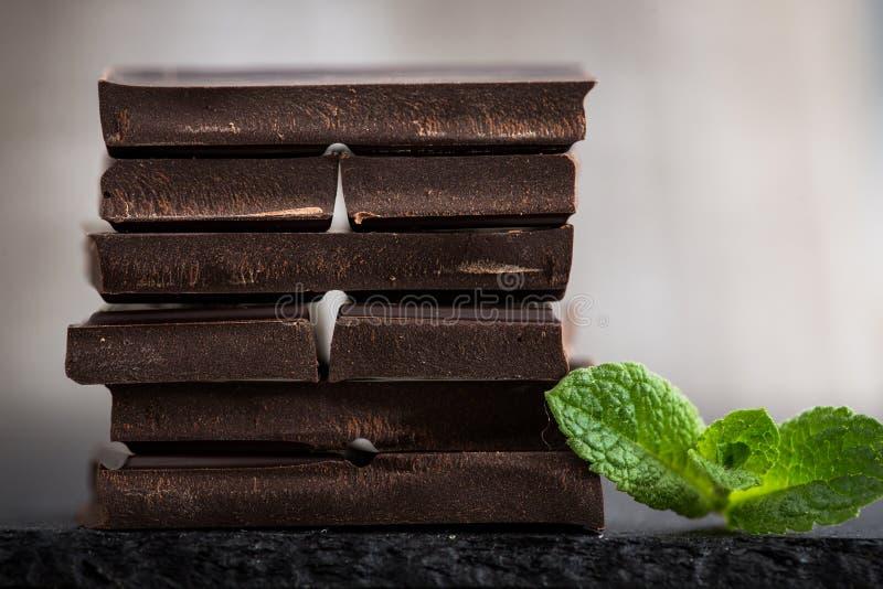 Bunt av chokladskivor med mintkaramellbladet mörk choklad över wo royaltyfria foton