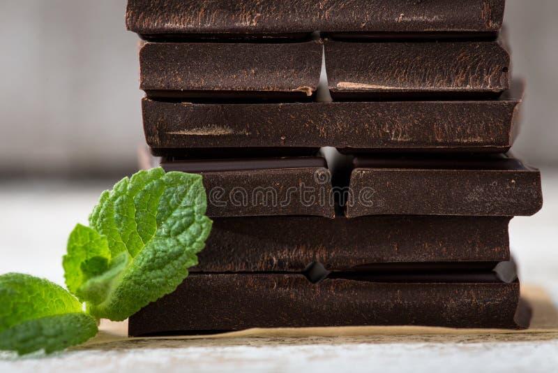 Bunt av chokladskivor med mintkaramellbladet mörk choklad över wo arkivbild