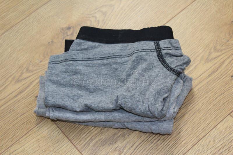 Bunt av den gråa manliga underkläderna på träbakgrund royaltyfri fotografi