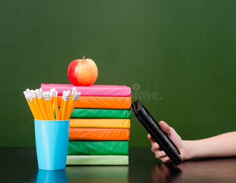 Bunt av färgrika böcker med den elektroniska bokavläsaren nära den tomma gröna svart tavlan prövkopia för text royaltyfri fotografi