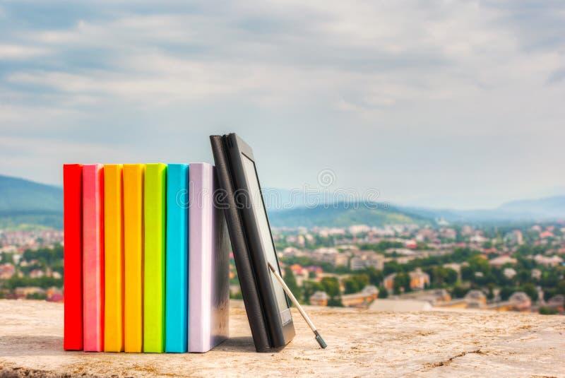 Bunt av färgrika böcker med eBookavläsaren arkivfoton