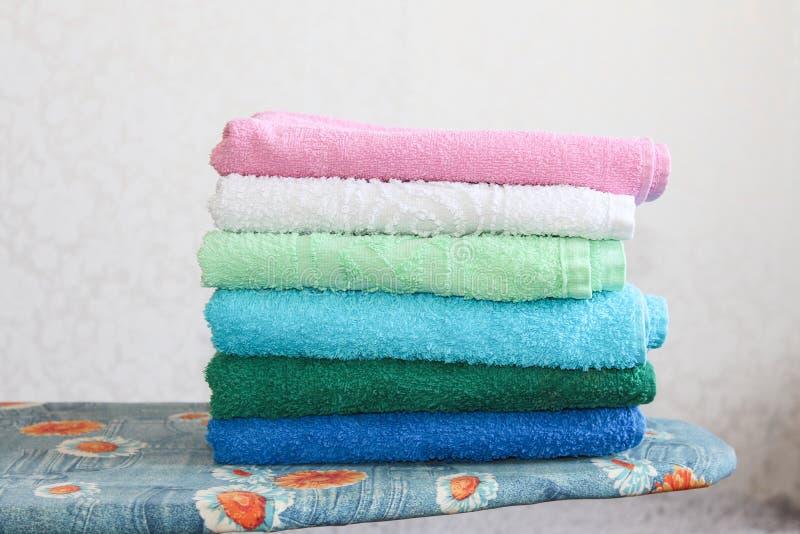 Bunt av färgrika rena handdukar på grå bakgrund Stryka kläder på strykbräda Bunt av rena handdukar på tabellen arkivbilder