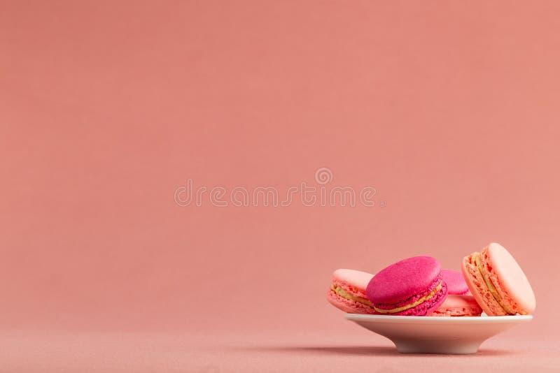Bunt av franska rosa macarons eller makron, i en liten platta över en rosa borddukbakgrund med stor copyspace arkivbild