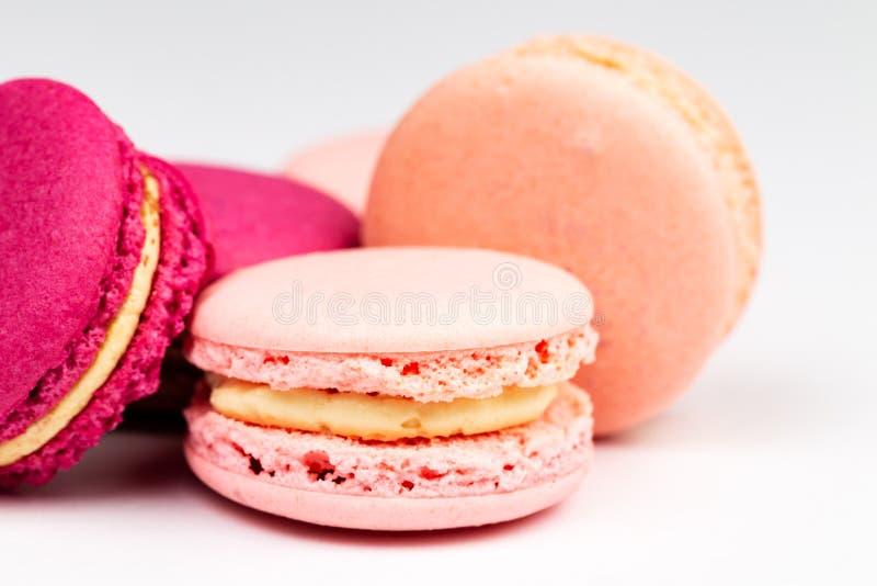Bunt av franska rosa och för fuchsia magentafärgade macarons eller makron, sidocloseup över en vit bakgrund royaltyfria foton
