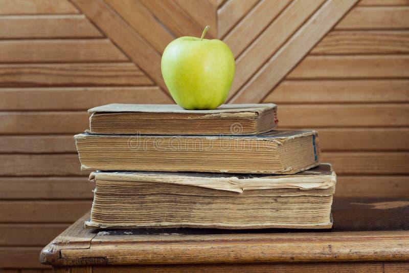 Bunt av gamla böcker och det gröna äpplet på gammal stol royaltyfri foto