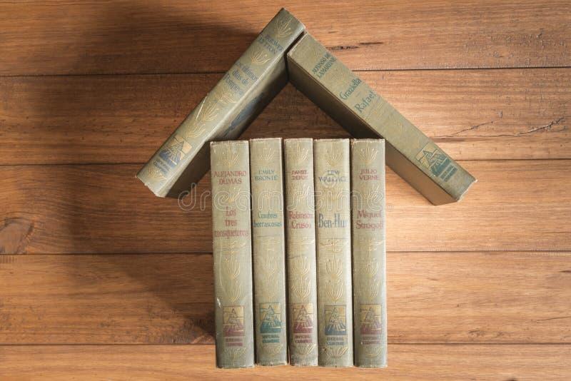 Bunt av gamla böcker som bildar diagramet av ett hus royaltyfri bild