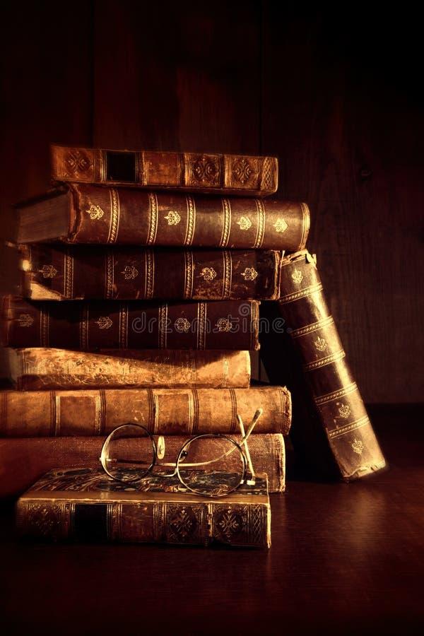 Bunt av gammala böcker med avläsningsexponeringsglas royaltyfri foto