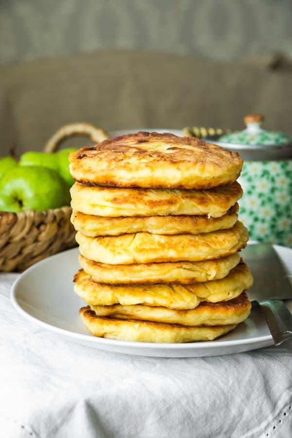 Bunt av guld- - läckra hemlagade kesostruvor eller pannkakor på den vita plattan, lantlig kökinre arkivbild