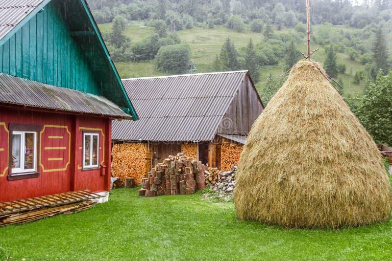 Bunt av hö nära traditionellt slavic hus fotografering för bildbyråer