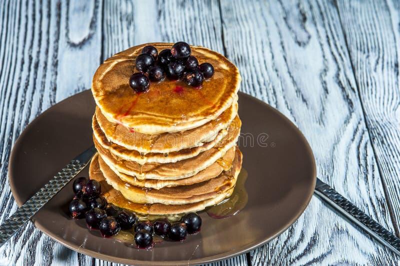 Bunt av hemlagade pannkakor med bär och honung på den bruna plattan på lantlig bakgrund royaltyfri foto