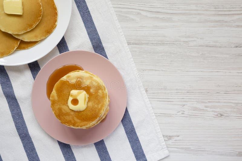 Bunt av hemlagade pannkakor med smör- och lönnsirap på en rosa platta, över huvudet sikt B?sta sikt, fr?n ?ver, framl?nges som ?r arkivfoton