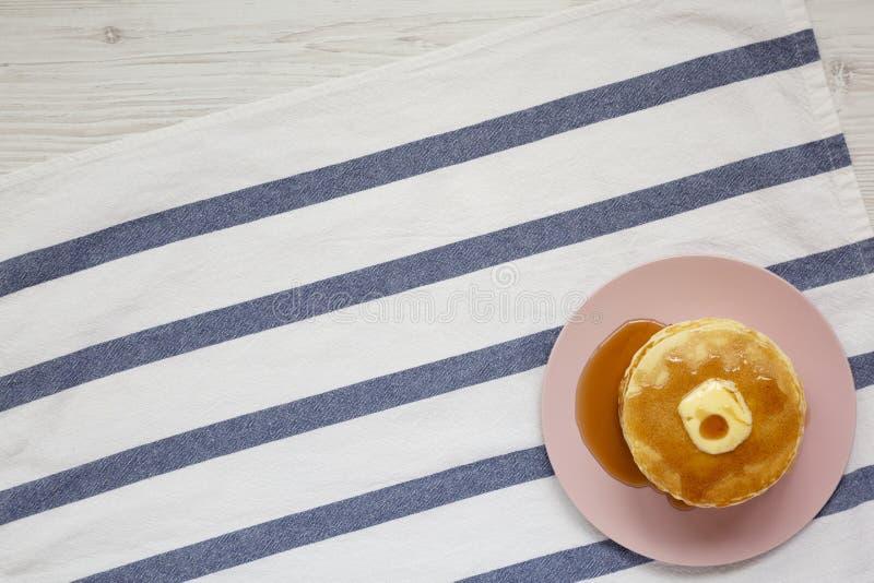 Bunt av hemlagade pannkakor med smör- och lönnsirap på en rosa platta, bästa sikt ?ver huvudet fr?n ?ver, framl?nges lekmanna- ko arkivbild