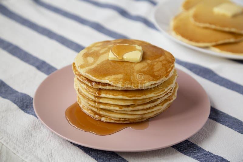Bunt av hemlagade pannkakor med smör- och lönnsirap på en rosa platta, sidosikt N?rbild arkivbild