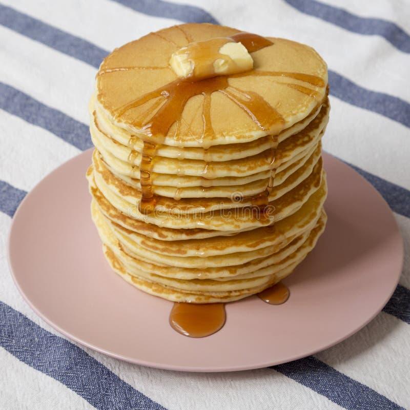 Bunt av hemlagade pannkakor med smör- och lönnsirap på en rosa platta, sidosikt N?rbild royaltyfri bild
