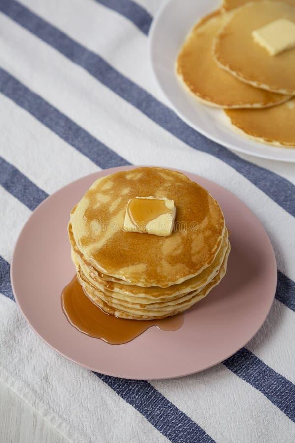 Bunt av hemlagade pannkakor med smör- och lönnsirap på en rosa platta, sikt för låg vinkel arkivfoton