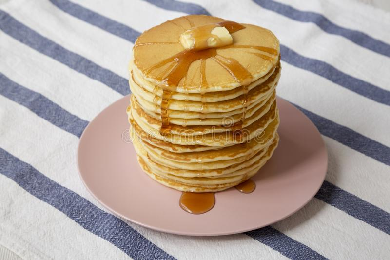 Bunt av hemlagade pannkakor med smör- och lönnsirap på en rosa platta, sikt för låg vinkel closeup arkivbild